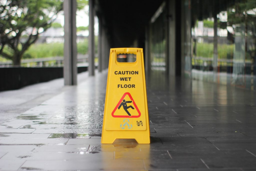 This image shows a slip or trip warning sign on the wet ground.